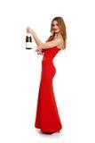Belle fille dans la robe rouge avec le champagne d'isolement sur le fond blanc, concept de vacances d'hiver Photos stock