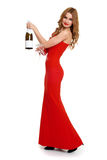 Belle fille dans la robe rouge avec le champagne d'isolement sur le fond blanc, concept de vacances d'hiver Image libre de droits