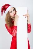 Belle fille dans la robe rouge dans un chapeau de Noël tenant des bannières Images stock