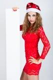 Belle fille dans la robe rouge dans un chapeau de Noël tenant des bannières Images libres de droits