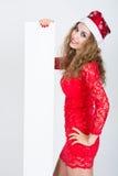 Belle fille dans la robe rouge dans un chapeau de Noël tenant des bannières Photo stock