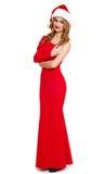 Belle fille dans la robe rouge et le chapeau de Santa d'isolement sur le fond blanc, concept de vacances d'hiver Photographie stock libre de droits