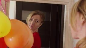 Belle fille dans la robe rouge regardant dans le miroir - portrait d'une jeune femme dans une robe de port de partie de pièce banque de vidéos