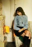 belle fille dans la robe rustique se reposant à la cheminée confortable dans vieux image stock