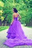 Belle fille dans la robe violette parmi dans le jardin Photographie stock