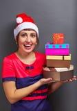 Belle fille dans la tête de Santa avec des boîte-cadeau Image stock