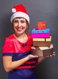 Belle fille dans la tête de Santa avec des boîte-cadeau Photos stock