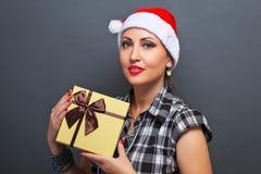 Belle fille dans la tête de Santa avec le boîte-cadeau Photographie stock libre de droits
