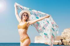 Belle fille dans le bikini, les verres et le chapeau en eau de mer claire Images stock