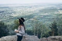 Belle fille dans le café de boissons de chapeau sur la montagne images stock