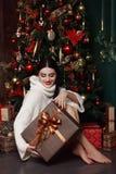 Belle fille dans le chandail se reposant à l'arbre de Noël Cadeaux, nouvelle année Image stock