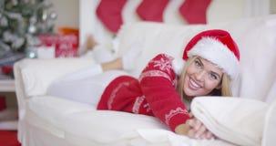 Belle fille dans le chapeau de Santa Claus dans son salon banque de vidéos