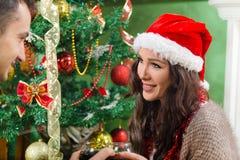 Belle fille dans le chapeau de Santa regardant le type sur Noël Photos libres de droits