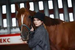 Belle fille dans le chapeau marchant avec un cheval Photographie stock libre de droits