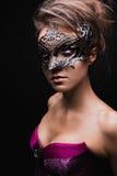 Belle fille dans le corset et masque avec le maquillage lumineux Photographie stock