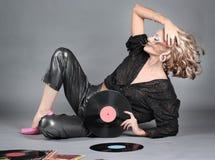 Belle fille dans le disque de vinyle de fixation d'équipement de disco. Image stock