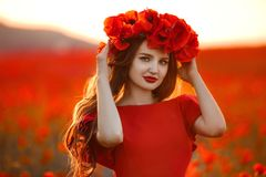 Belle fille dans le domaine rouge de pavot au coucher du soleil En heureuse gratuite de femme Photos stock