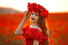 Belle fille dans le domaine rouge de pavot au coucher du soleil En heureuse gratuite de femme Images stock