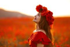 Belle fille dans le domaine rouge de pavot au coucher du soleil En heureuse gratuite de femme Photos libres de droits