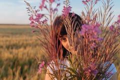 Belle fille dans le domaine se cachant derrière des fleurs Photographie stock libre de droits