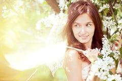 Belle fille dans le jardin abondant de source Photographie stock