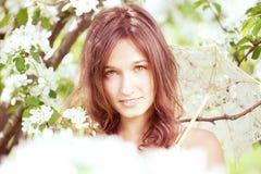 Belle fille dans le jardin abondant de source Photo stock