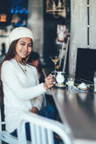 Belle fille dans le thé potable de longue douille blanche dans un café Photos stock