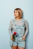Belle fille dans les combinaisons avec les roses rouges dans des mains sur un fond bleu Les mains du ` s de femmes tiennent un bo Photo stock