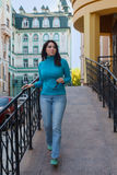 Belle fille dans un col roulé bleu près de la balustrade Images stock
