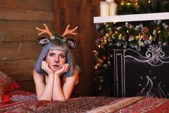 Belle fille dans un costume de cerfs communs de Noël sur le lit Photographie stock