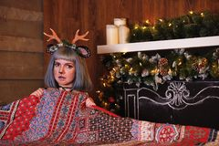 Belle fille dans un costume de cerfs communs de Noël sur le lit Photo stock