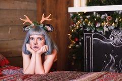 Belle fille dans un costume de cerfs communs de Noël sur le lit Images stock