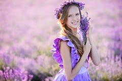 Belle fille dans un domaine de lavande sur le coucher du soleil Images stock