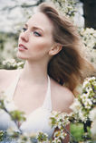 Belle fille dans un jardin de floraison de ressort Photographie stock