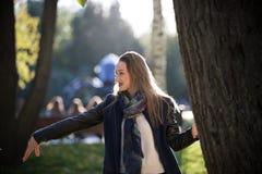 Belle fille dans un manteau à côté d'un arbre en parc ensoleillé d'automne images stock