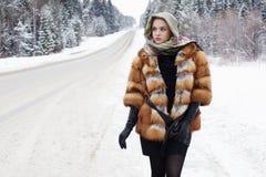 Belle fille dans un manteau de fourrure attendant la voiture sur une route d'hiver dans la forêt Photographie stock libre de droits