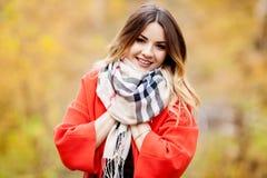 Belle fille dans un manteau et une écharpe rouges pendant le jour d'automne de parc Photos libres de droits