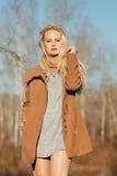 Belle fille dans un manteau posant dans la perspective d'une nature de ressort Photos stock