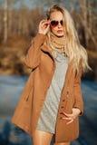 Belle fille dans un manteau posant dans la perspective d'une nature de ressort Image stock