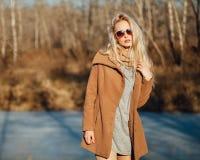 Belle fille dans un manteau posant dans la perspective d'une nature de ressort Photo stock
