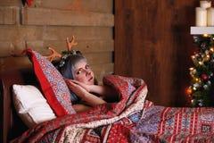 Belle fille dans un mensonge de costume de cerfs communs de Noël dans le lit Image libre de droits