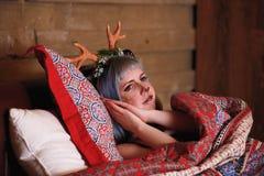 Belle fille dans un mensonge de costume de cerfs communs de Noël dans le lit Image stock