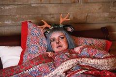 Belle fille dans un mensonge de costume de cerfs communs de Noël dans le lit Photographie stock