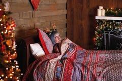 Belle fille dans un mensonge de costume de cerfs communs de Noël dans le lit Images libres de droits