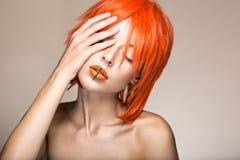 Belle fille dans un style cosplay de perruque orange avec les lèvres créatives lumineuses Image de beauté d'art image libre de droits