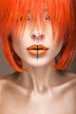 Belle fille dans un style cosplay de perruque orange avec les lèvres créatives lumineuses Image de beauté d'art Photos stock