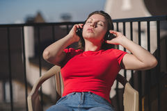 Belle fille dans un T-shirt rouge et des écouteurs Une fille sur le balcon écoutant la musique et chante Images stock