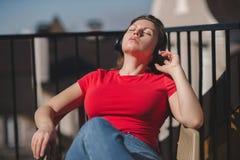 Belle fille dans un T-shirt rouge et des écouteurs Une fille sur le balcon écoutant la musique et chante Photos libres de droits