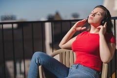 Belle fille dans un T-shirt rouge et des écouteurs Une fille sur le balcon écoutant la musique et chante Photographie stock libre de droits