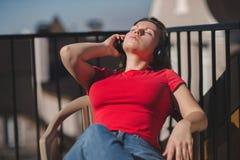 Belle fille dans un T-shirt rouge et des écouteurs Une fille sur le balcon écoutant la musique et chante Photos stock